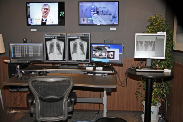Executive Reading Room:遠隔診断、読影医の未来型のワークステーションを今後提案していく。遠隔地の医師同士がリアルタイムで読影画面やレポートを共有、遠隔地の病院への撮影指示をテレビ会議室システムでお互いの顔を見ながらやり取りができる。また、システムへのログインでは、IDやパスワードではなくネットワークカメラを利用した、顔認証システムでシステムを制御し、セキュリティの強化と利便性の向上を図る。